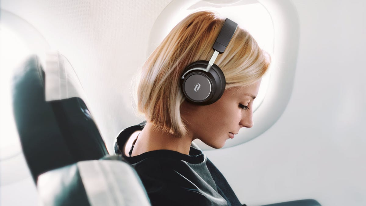 A woman sitting on a plane wearing a pair of Taotronics ANC headphones.
