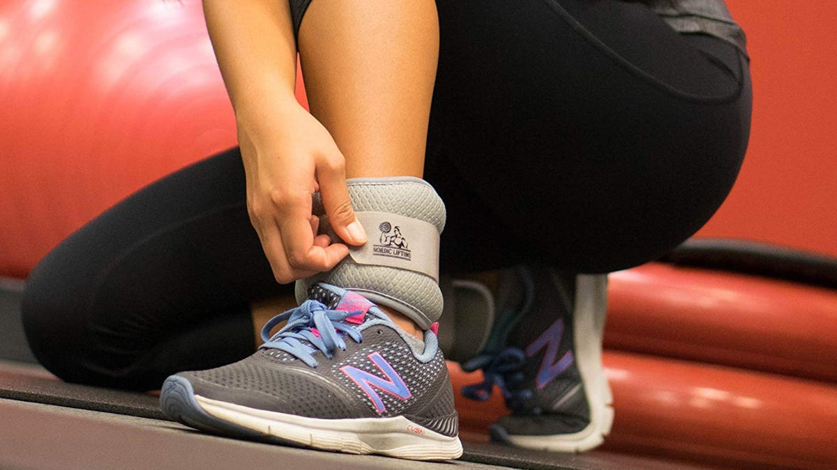 Woman adjusting her NordickTrack Lifting ankle weights.