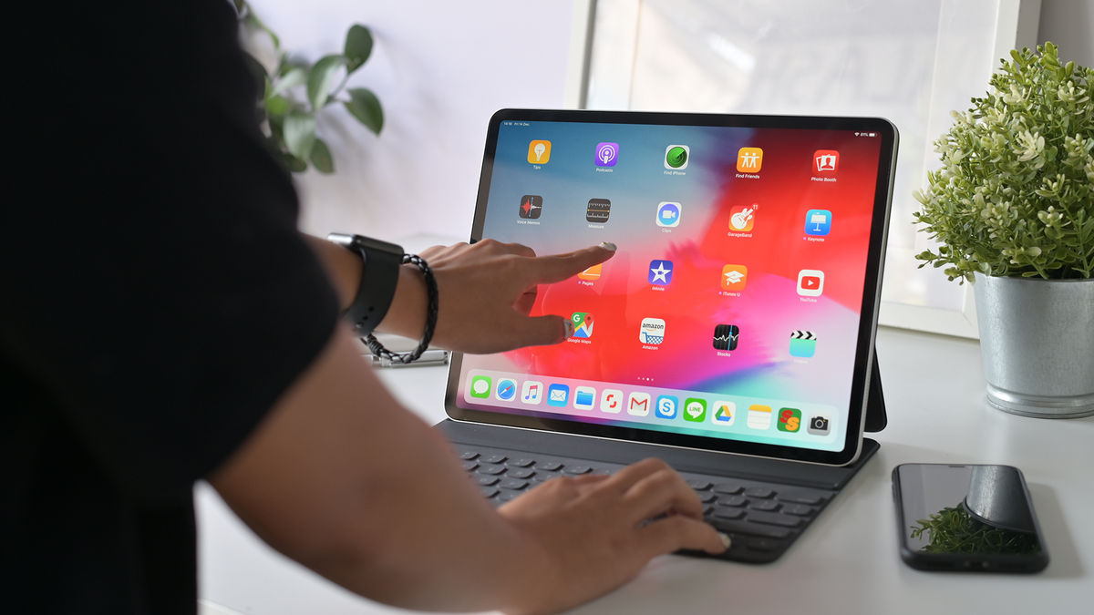 A woman uses the iPad Pro with an official Apple keyboard.