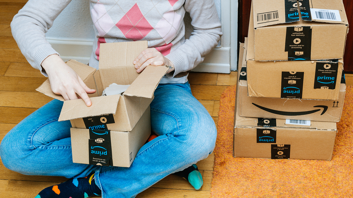 A person sitting on the floor next to a stack of Amazon boxes and opening one.