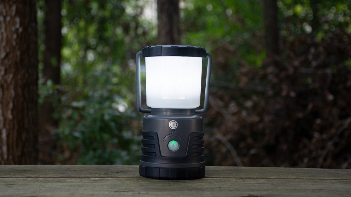 30-Day DURO Dual Power LED Lantern sitting on a picnic table with trees behind it.