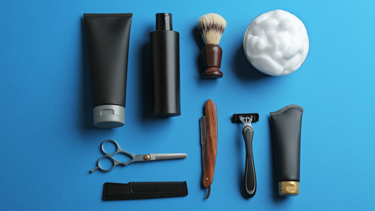 Various bottles, a shaving cream brush, a men's razor, a straight-razor, a comb, and trimmers lying on a blue blue background.