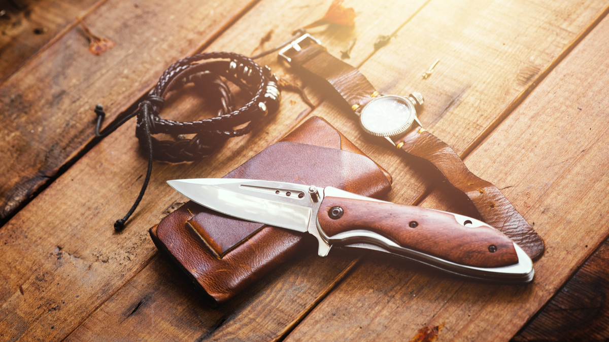 A premium knife sitting on a wallet, next to a watch and a leather bracelet on a wooden table.