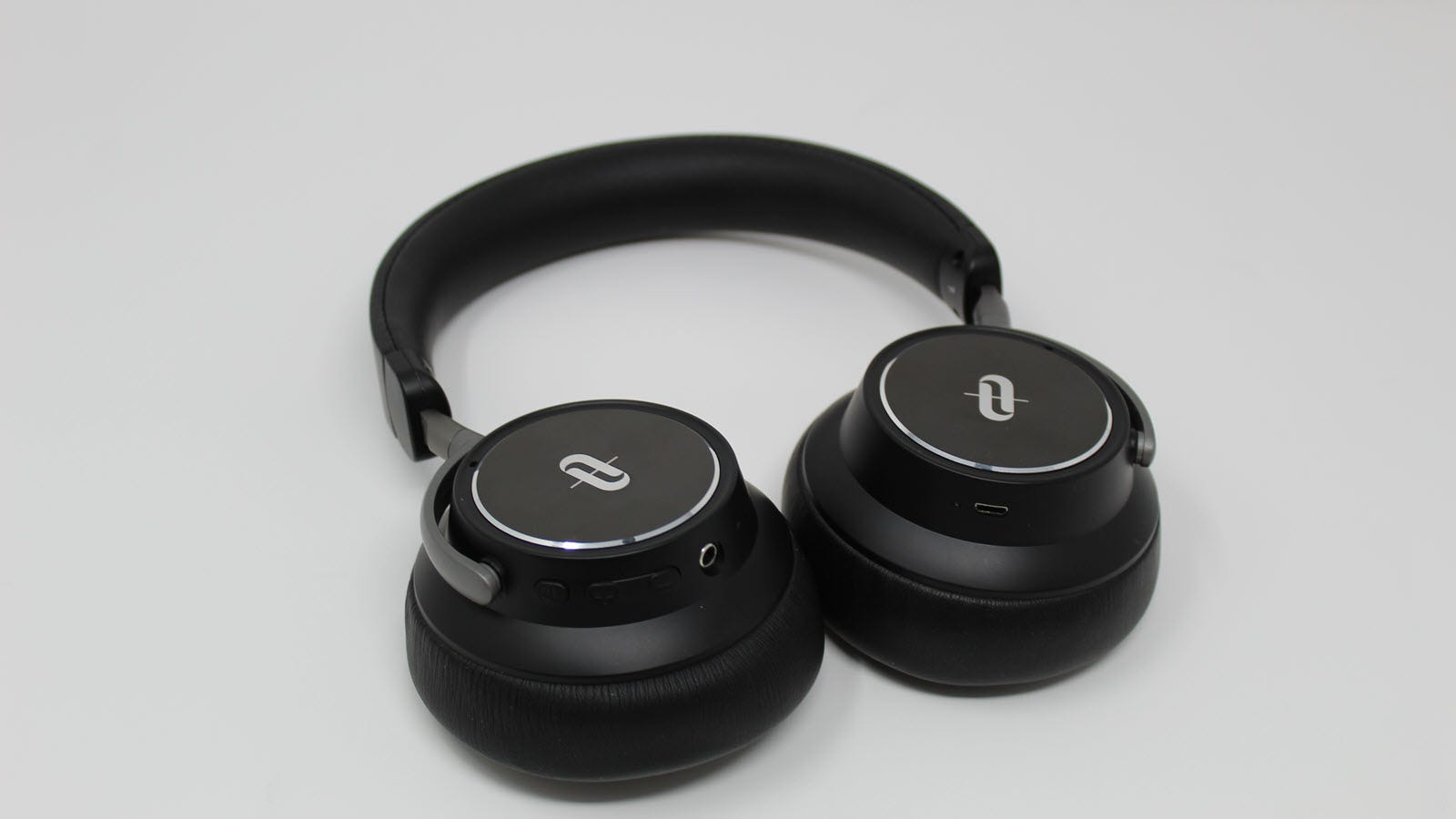 A pair of Taotronics ANC headphones with volume up, down, and power button showing.