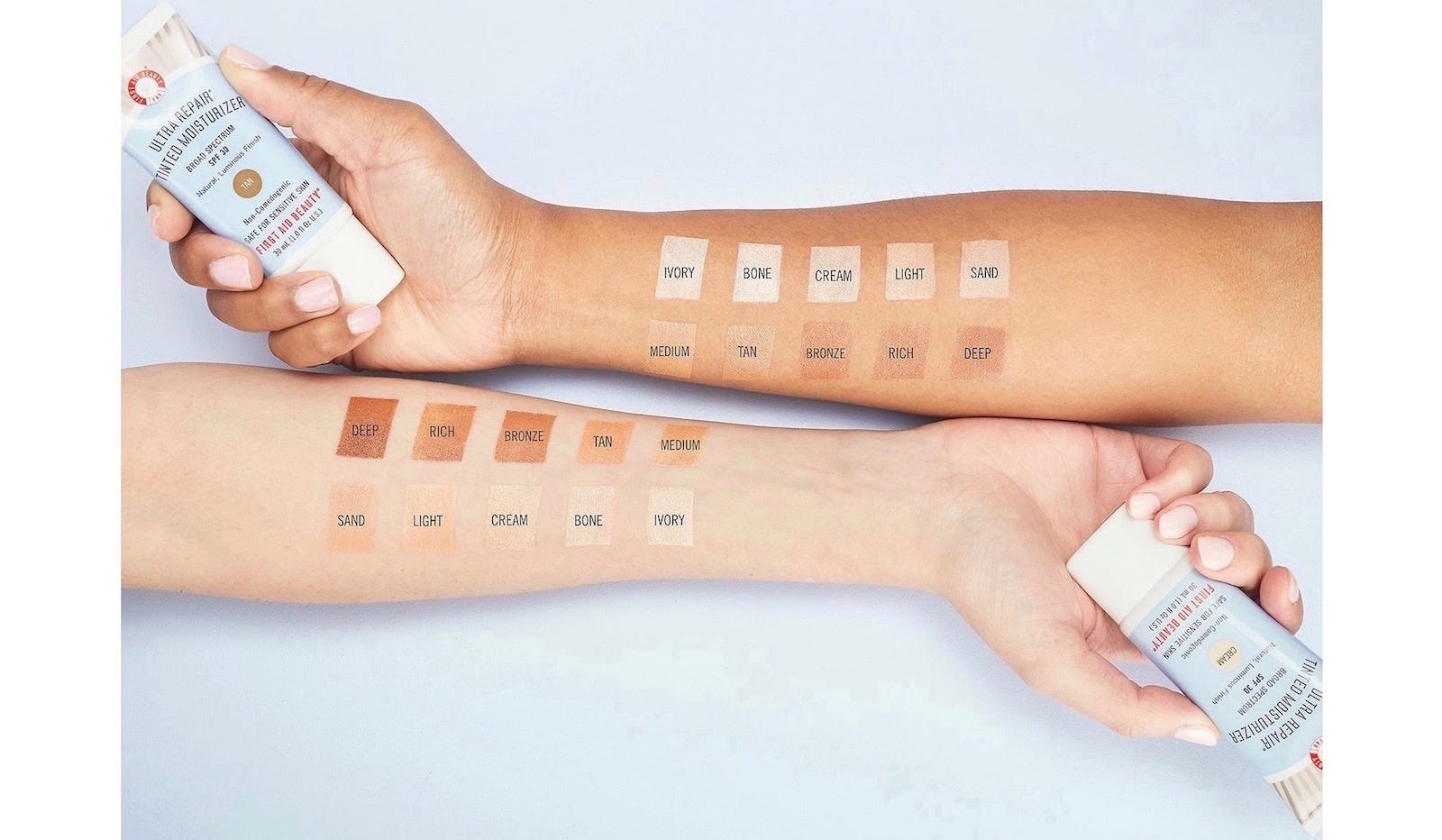 Two arms extended showing the different shades of the product, and the hands each holding a tube of First Aid Beauty Ultra Repair Tinted Moisturizer.