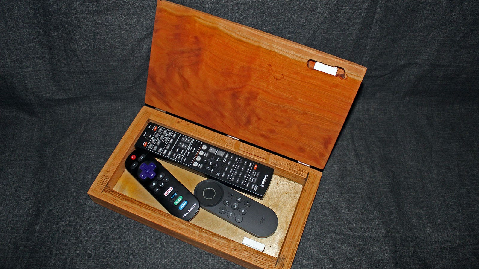 The inside of the box, with three TV remotes, and a Wyze contact sensor.