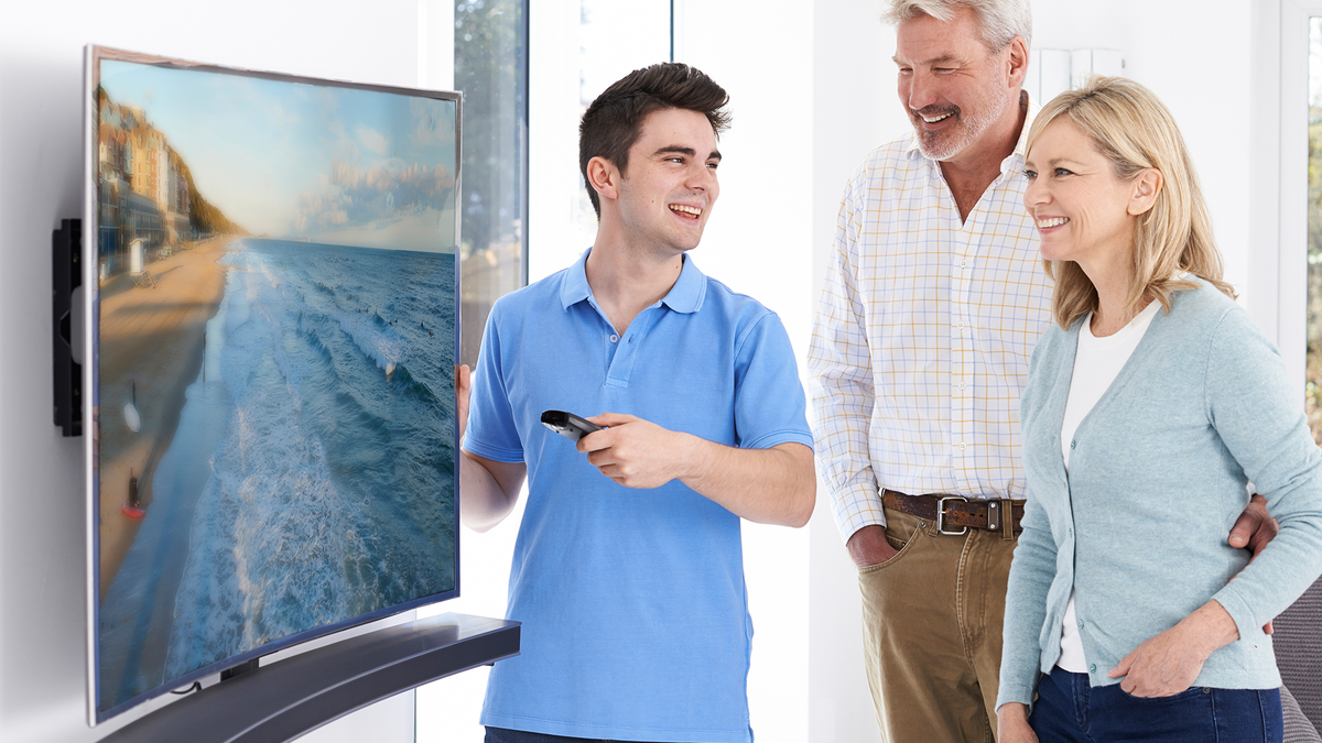 A man shows his parents his neat new curved TV. They seem proud.