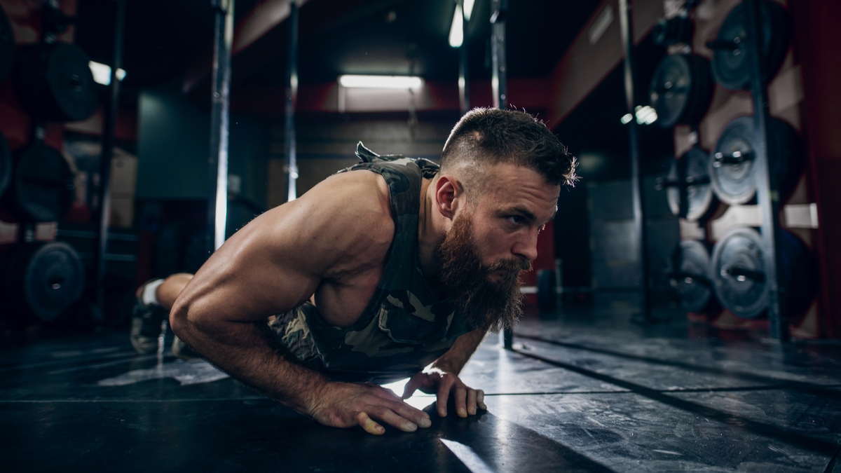 Muscular man wearing a weighted vest while doing a push-up