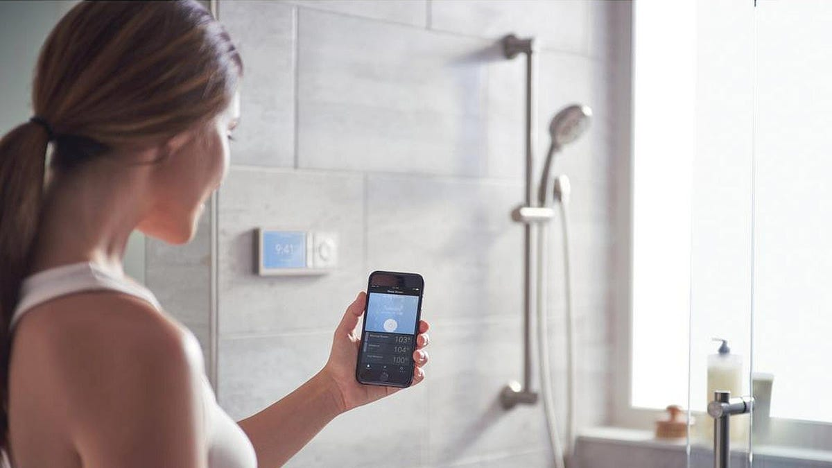 A woman controlling her shower by smartphone.