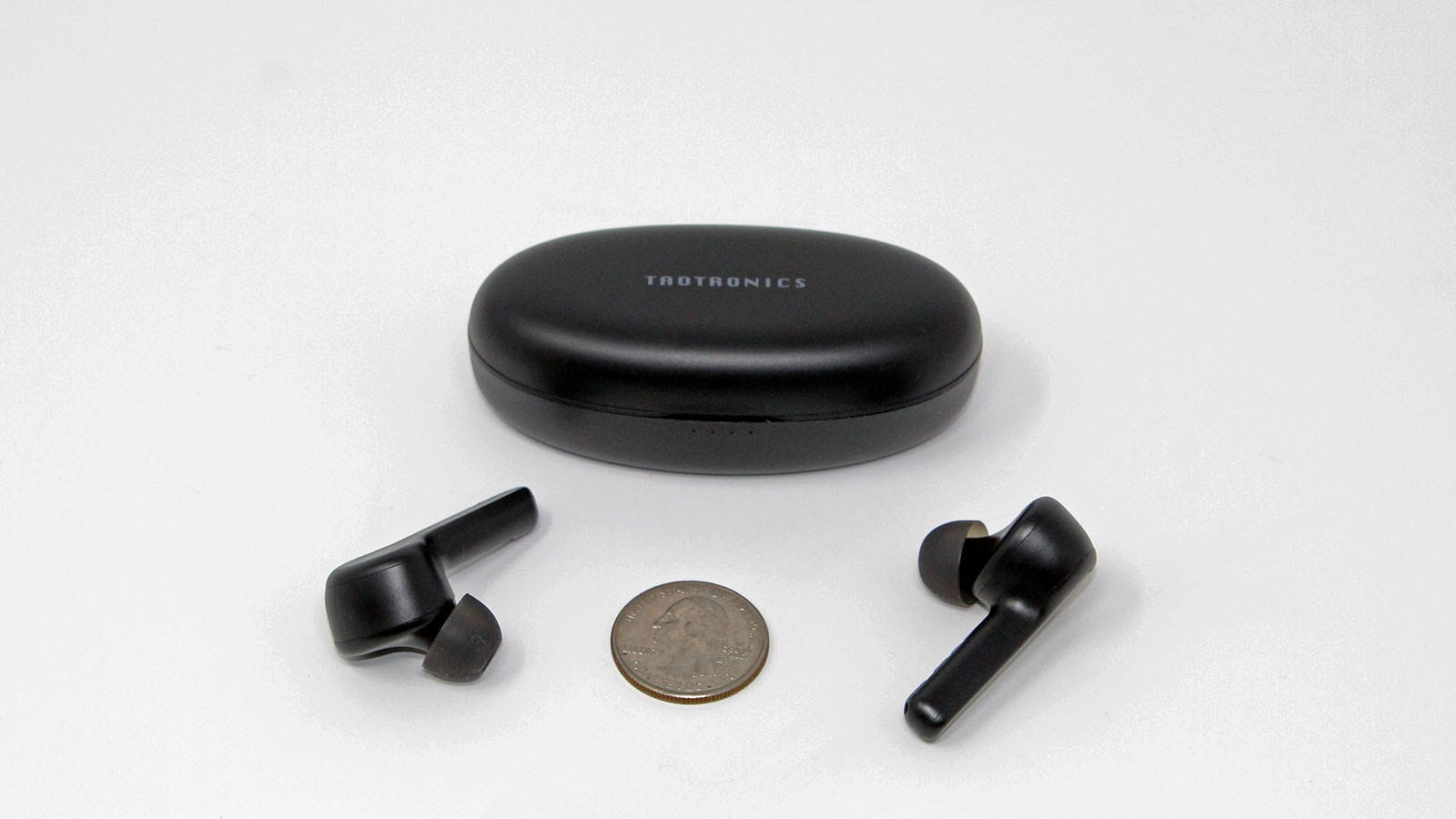 The TaoTronics case, earbuds, and a quarter.