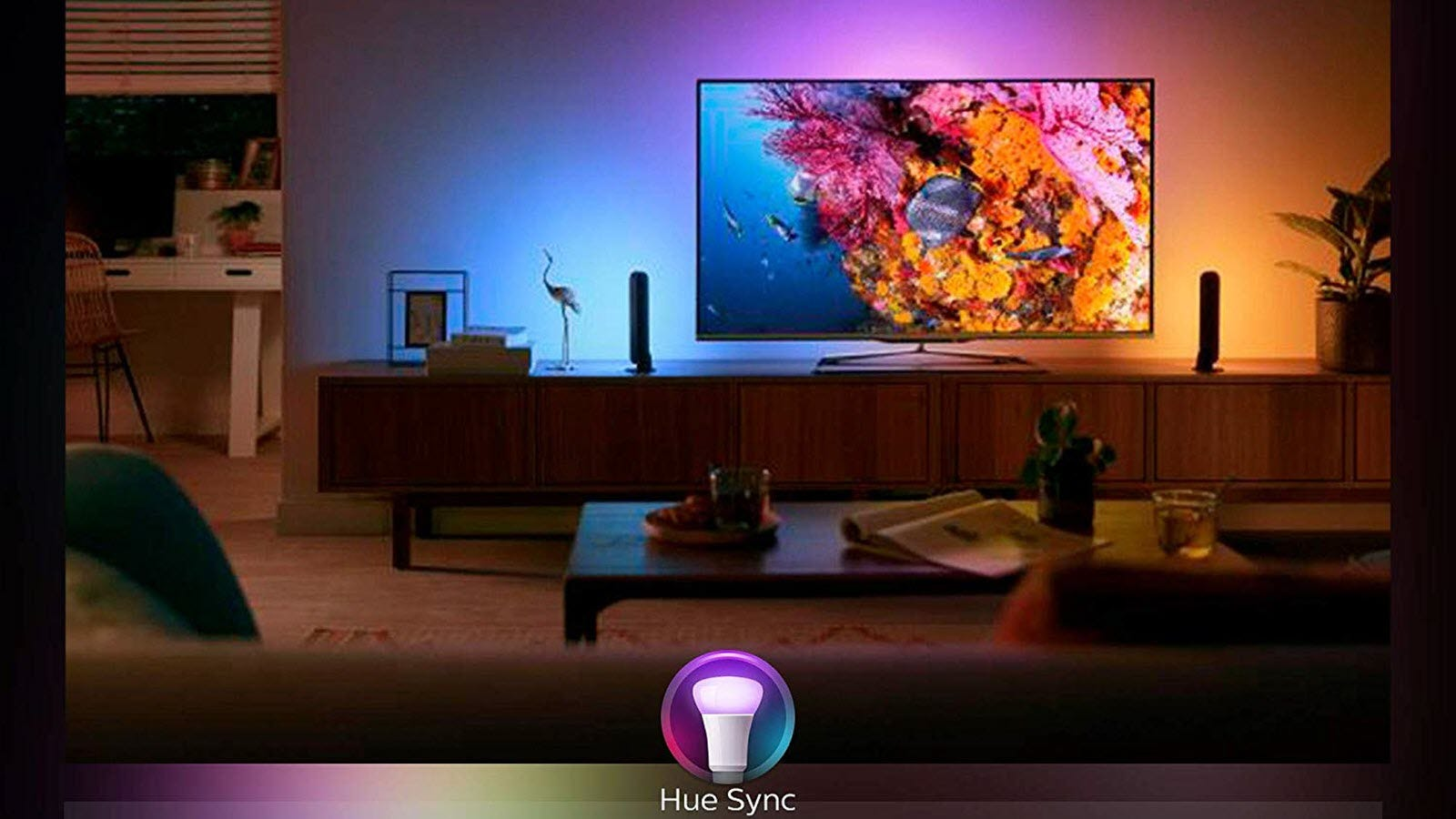 A living room lit with several smart lights in blue, purple, and orange.
