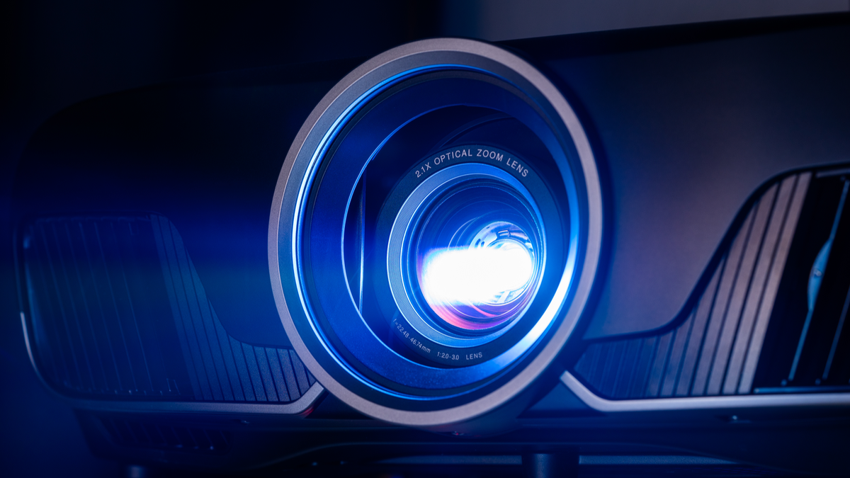 A projector lens bathed in blue light.