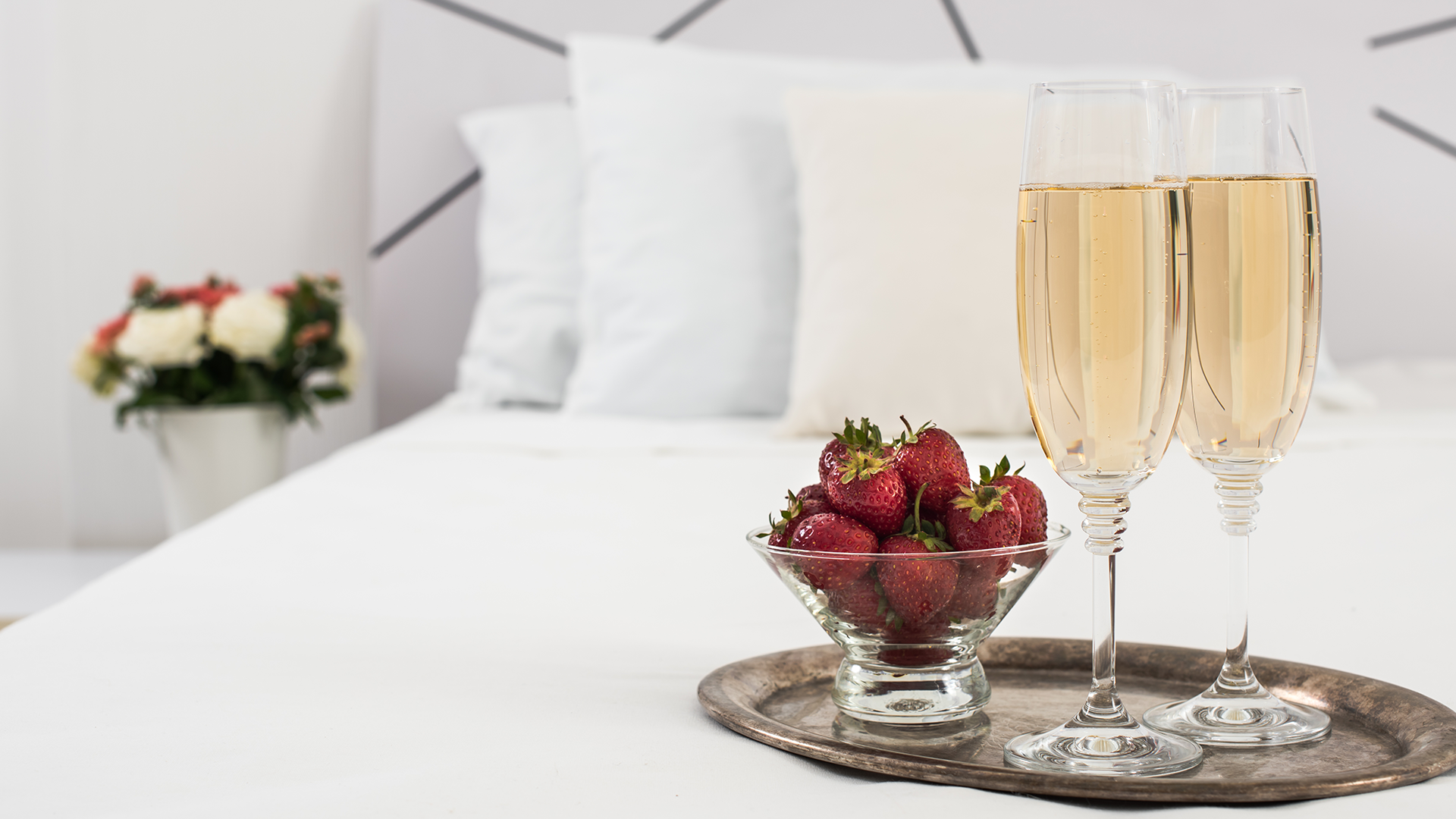Glasses of champagne and a bowl of strawberries sit on an expensive mattress.