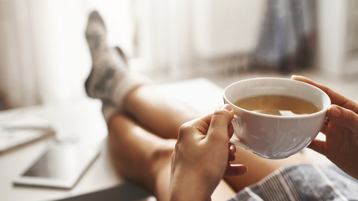 A person kicks back and drinks their morning coffee.