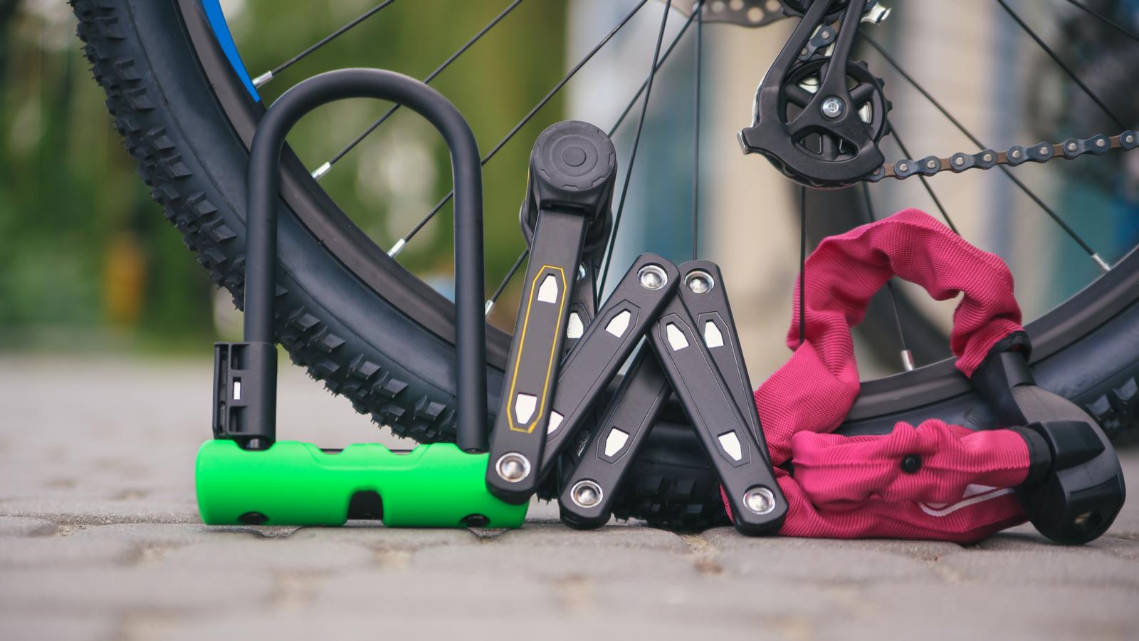 Bike locks on the ground next to a bike wheel.