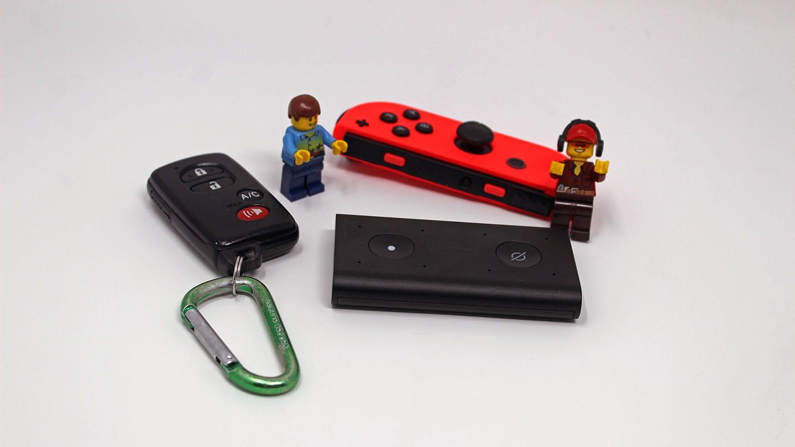 An Echo next to a Prius key fob, Nintendo Joy-Con and two lego Minifigs.