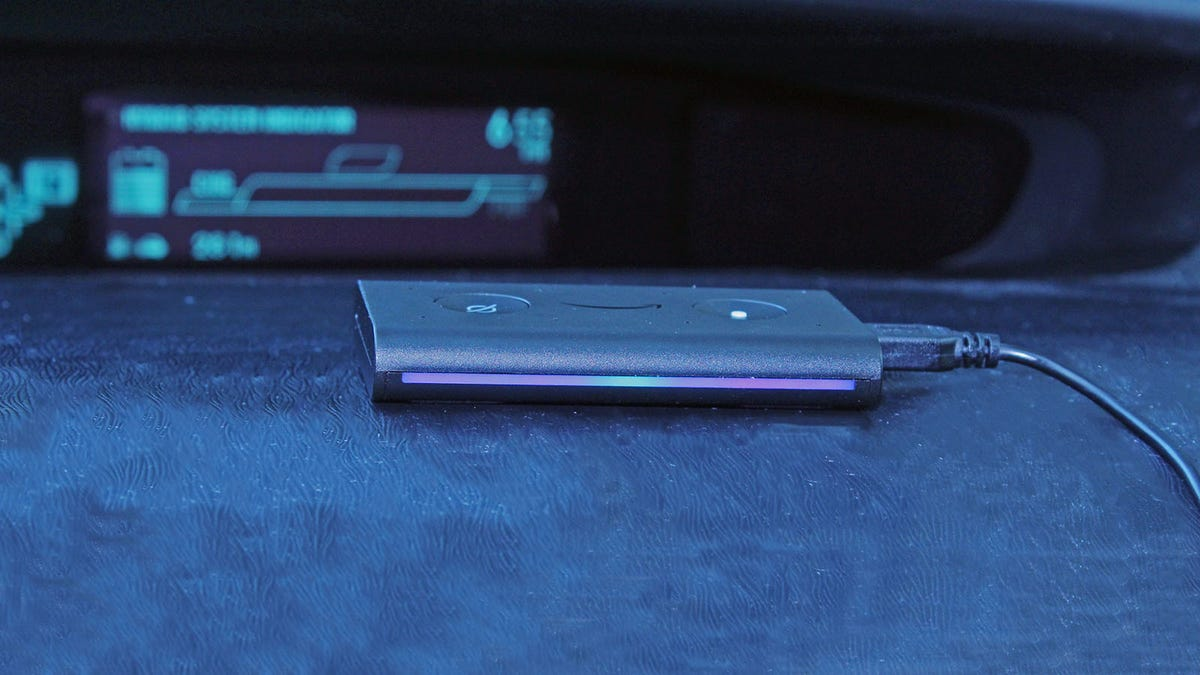 An Echo Auto sitting on a car dash, with a blue light showing.