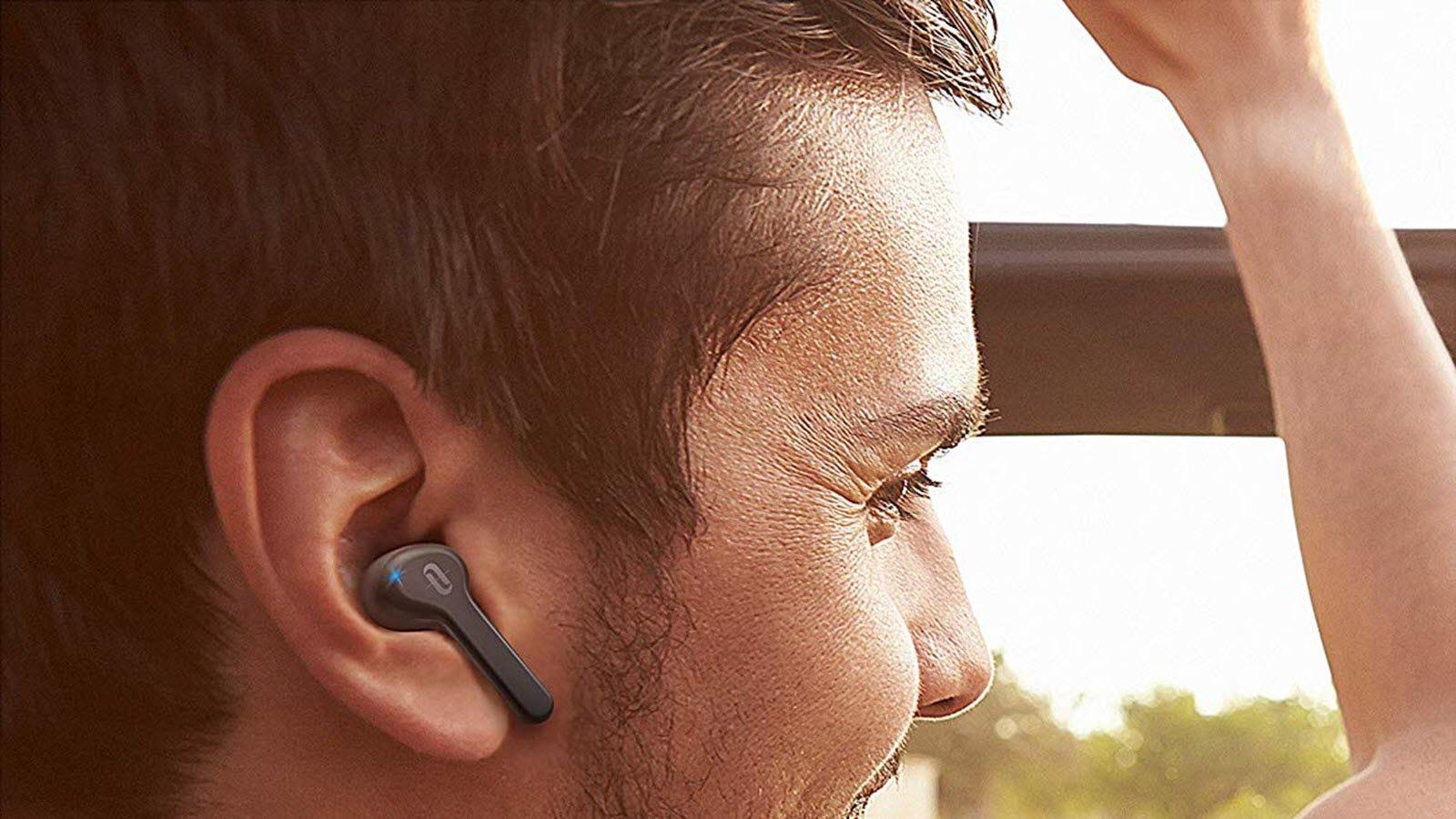 A TaoTronics SoundLiberty 53 earbud in a man's ear.