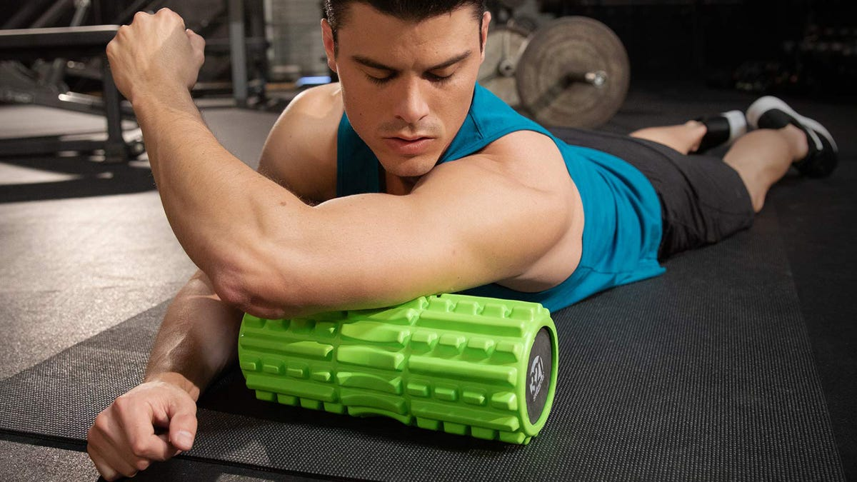 A Man lying on a workout mat using a 321 Strong Foam Roller with his arm.