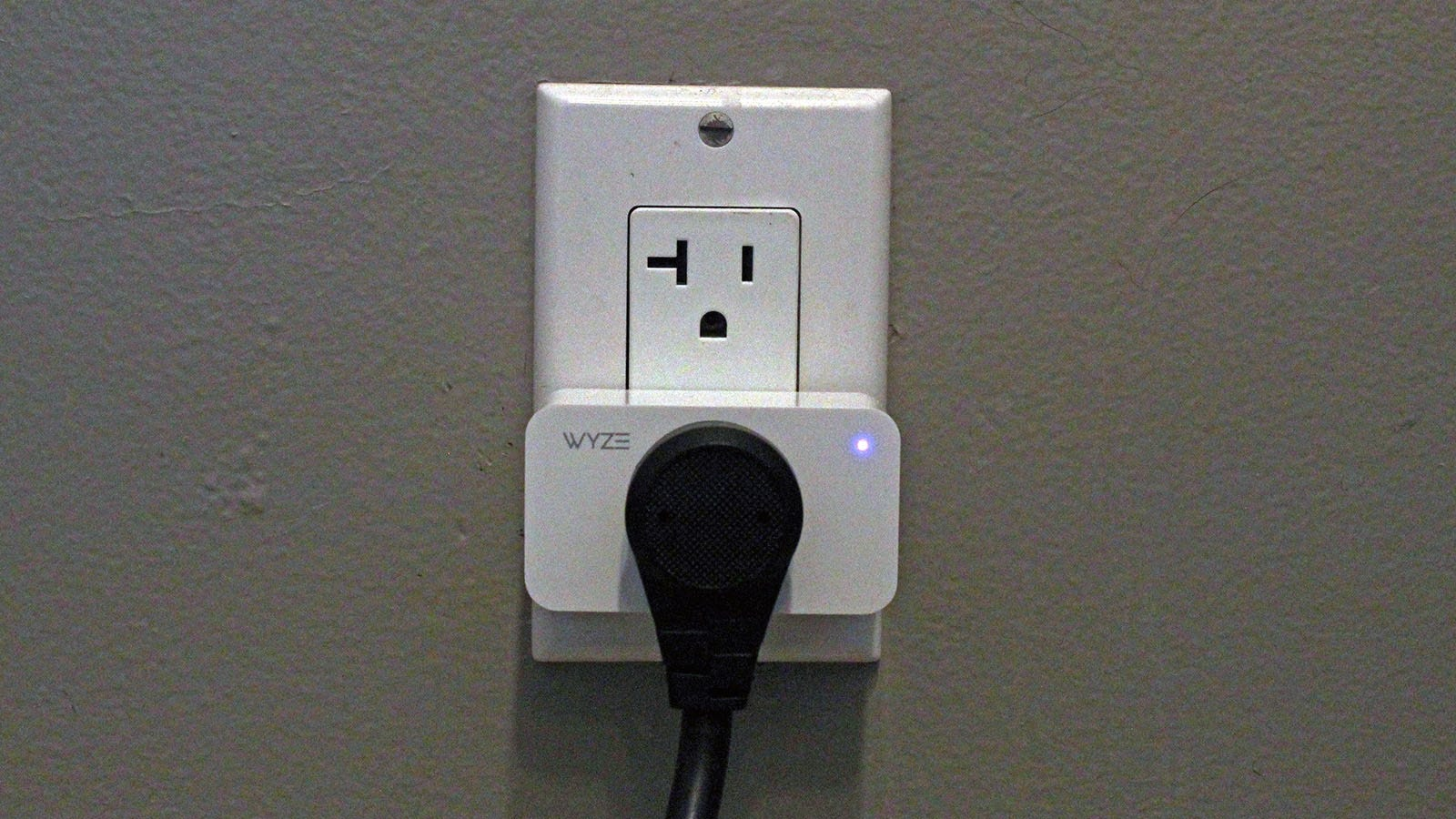 A Wyze Plug in an outlet, with a device plugged into it.