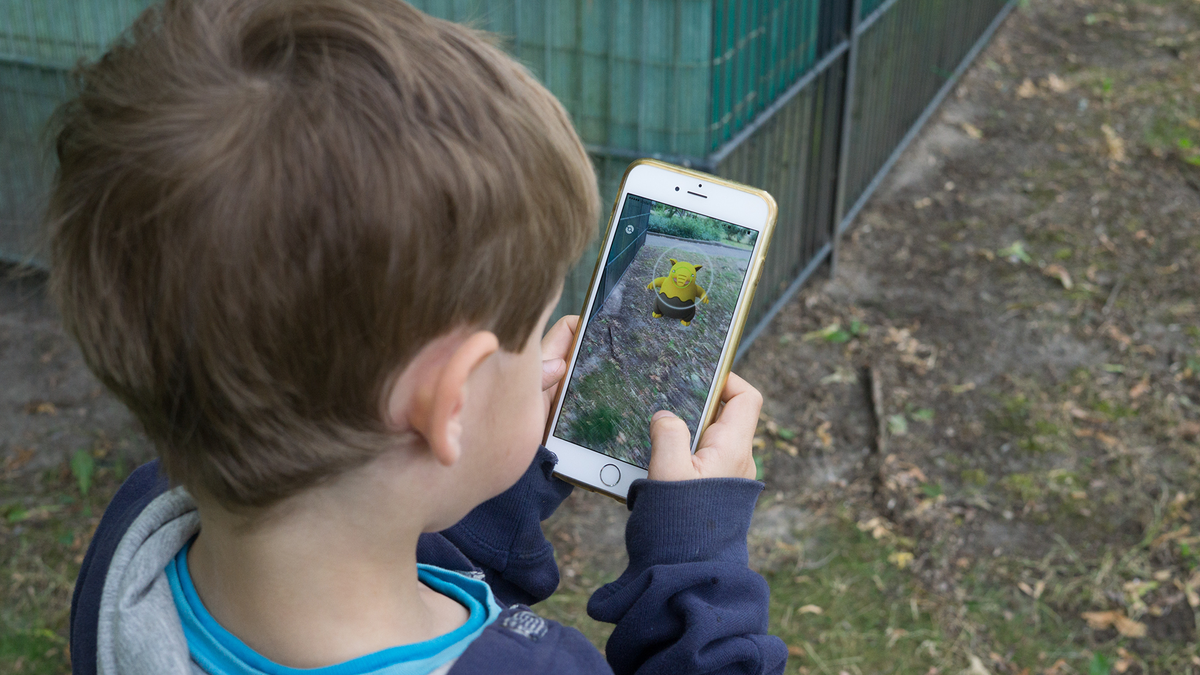 A young boy plays Pokemon GO outside