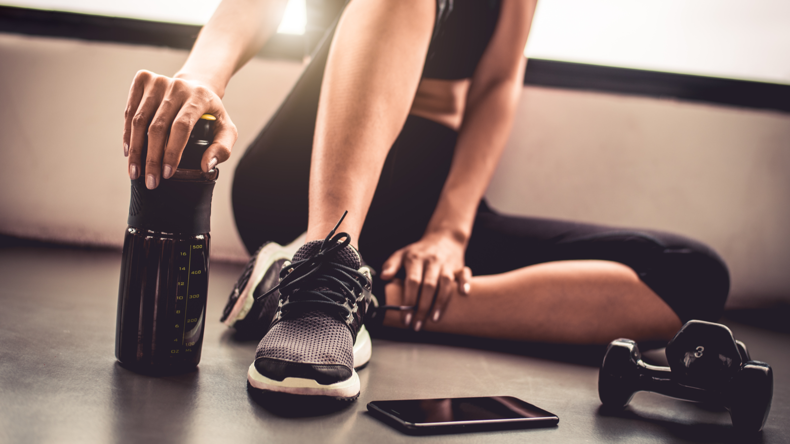 A woman sitting on the floor next to dumbbells and a smartphone, her hand resting on a water bottle.