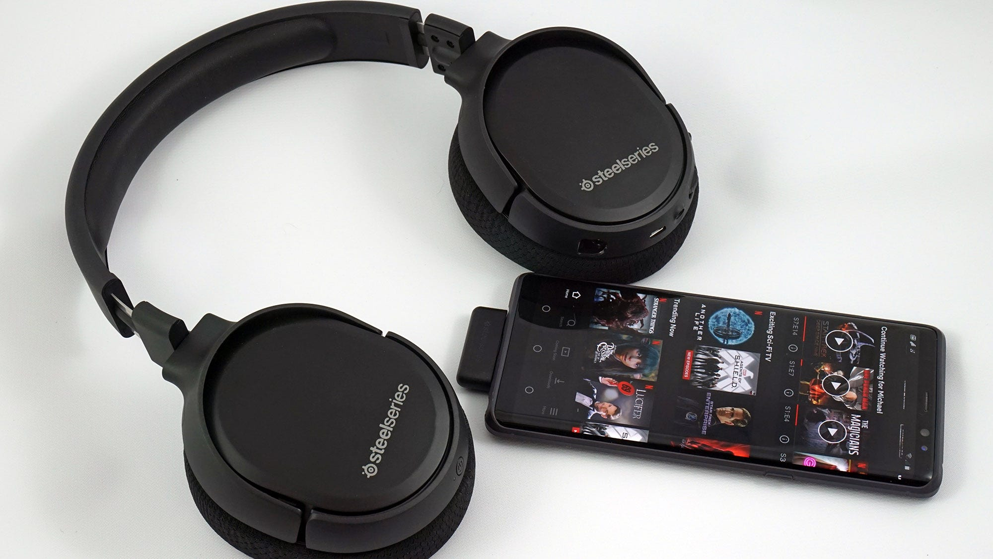 The SteelSeries Arctis 1 Wireless Headset next to a smartphone.
