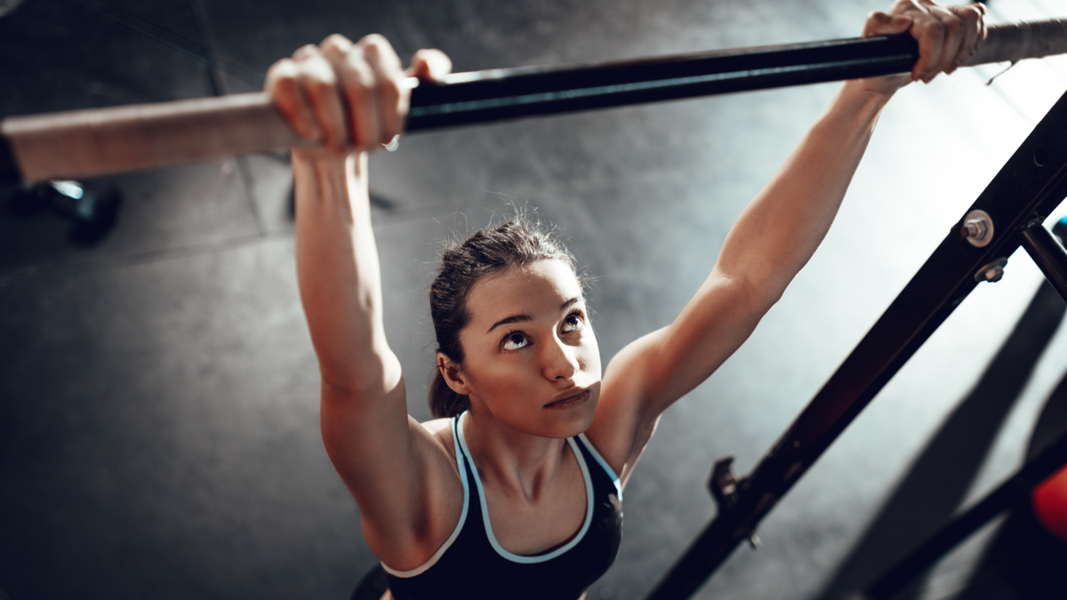 Athletic woman on a pull up bar