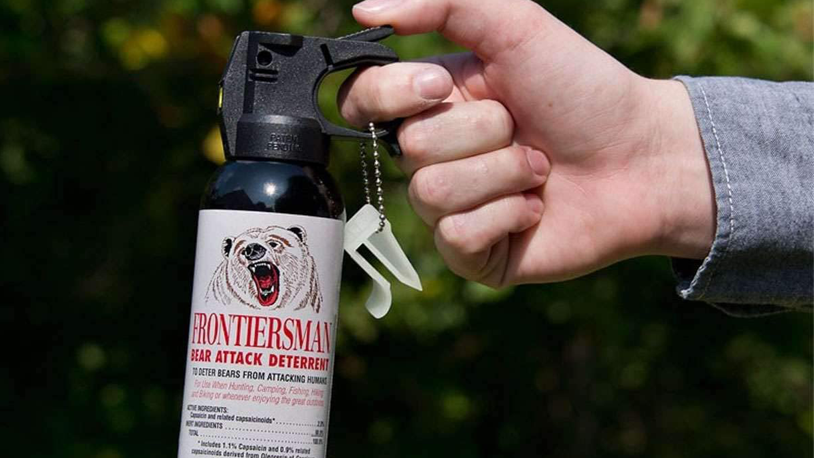 Person's hand pulling trigger on can of bear mace