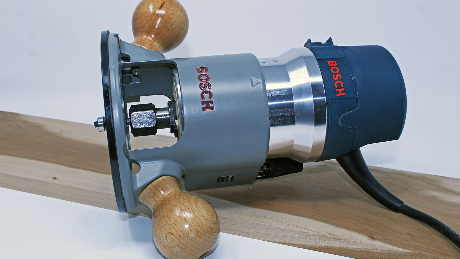A Bosch 1617EVS with bit inserted, laying on a cherry plank.