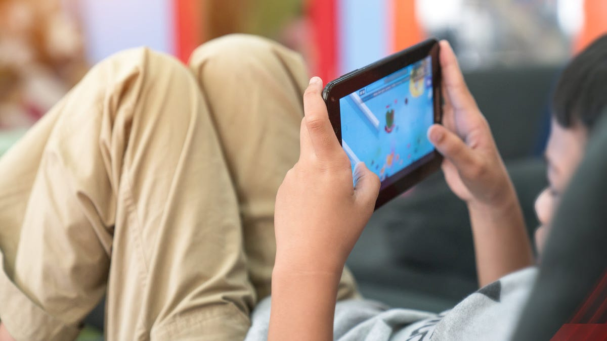 A young child leaning back and playing a game on a small tablet.