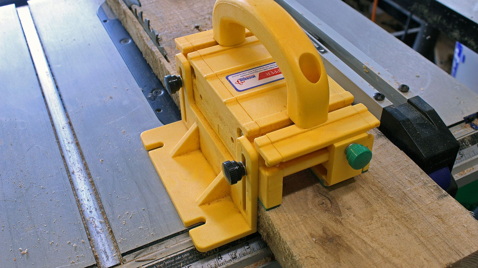 A GRR-RIPPER block pushing wood through a blade.