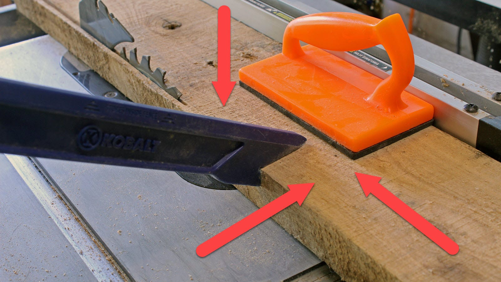 A piece of wood running through a tablesaw with a push stick and block, and three arrows pointing down, sideways and forward.