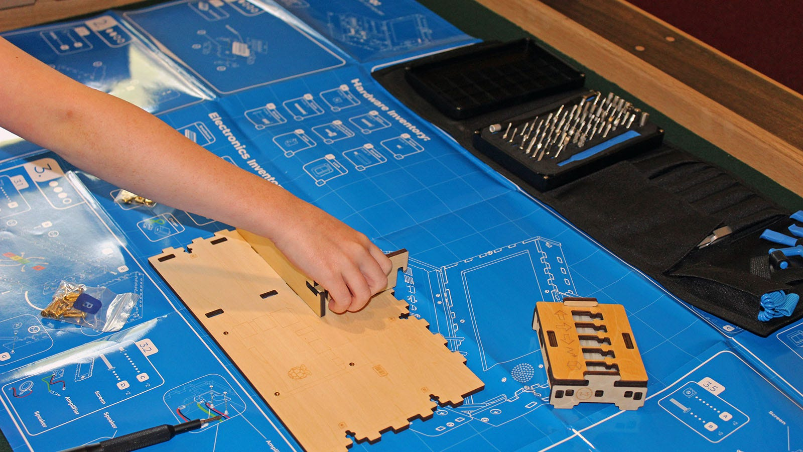 A Blueprint poster, with pieces of the Piper Kit being assemble on top of it.