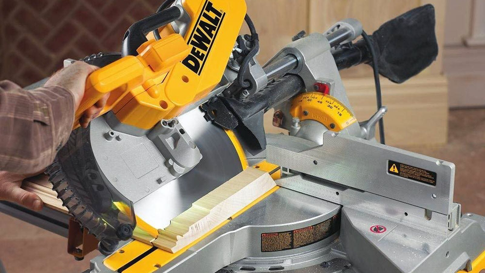 A DeWalt miter saw tilted at and angle to cut through floor molding.