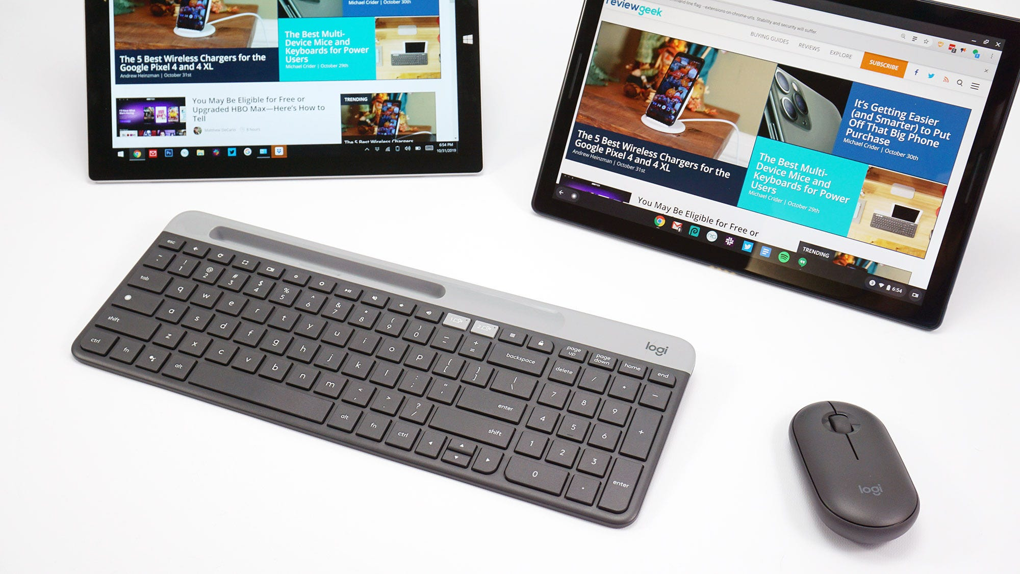 The Logitech K580 keyboard and a mouse in front of two tablets.