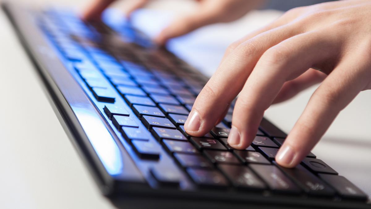 Руки человека печатают на клавиатуре с синей подсветкой