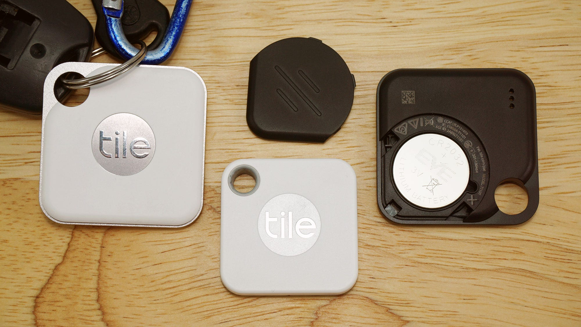 Two Tile Pros compared to the Mate, one with battery exposed.
