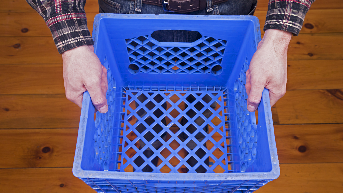 A man holding a plastic blue milk crate.