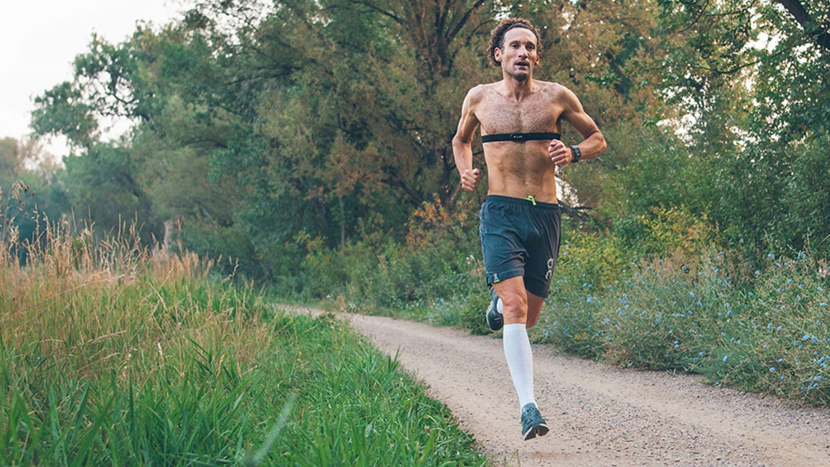A man running with a chest strap HR tracker