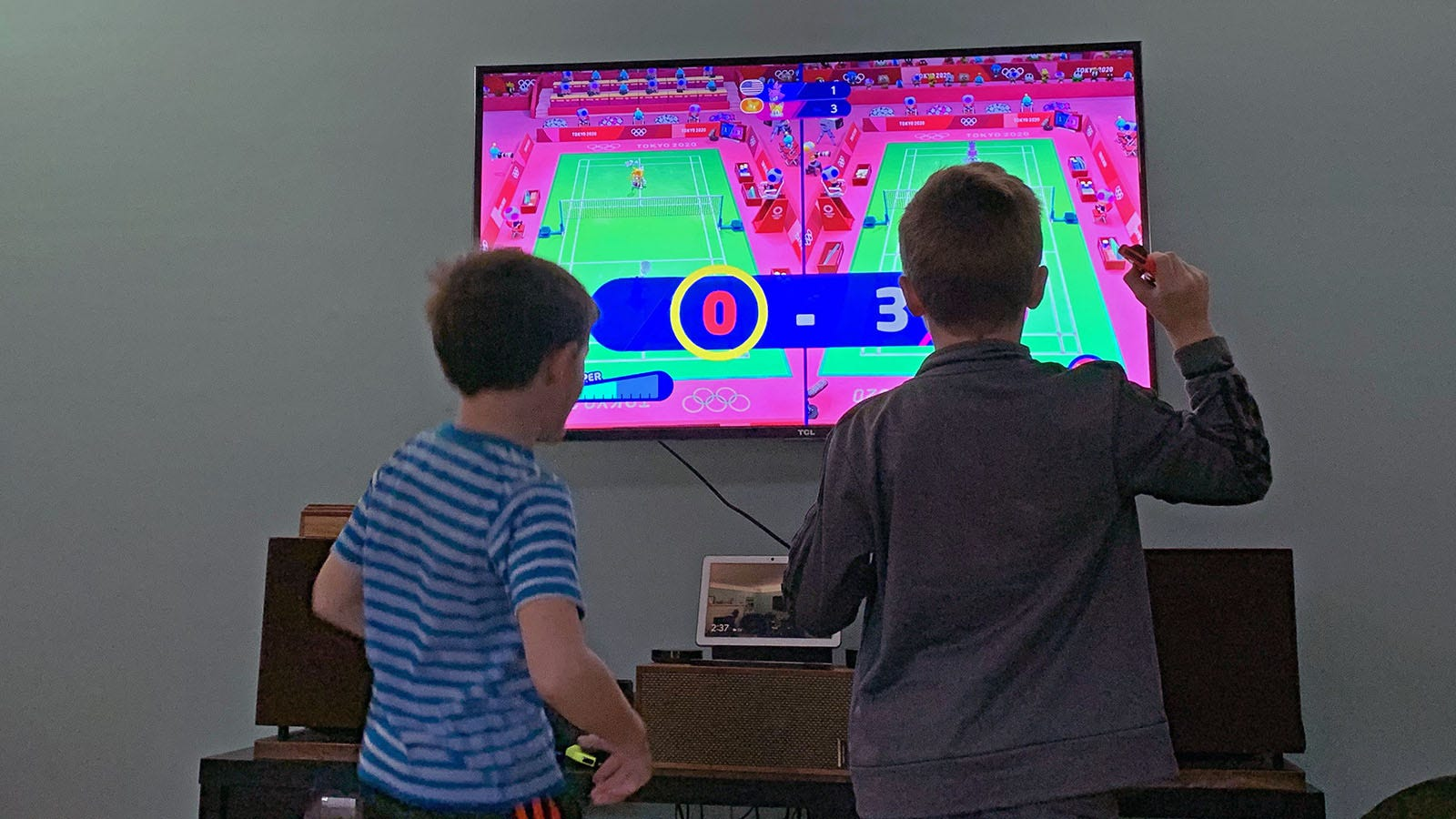 Two young boys playing a game of tennis on Nintendo Switch