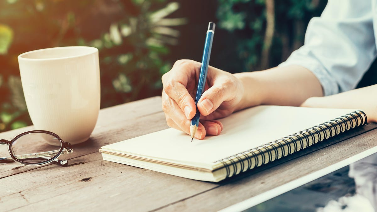 Woman hand with pencil writing on notebook at coffee shop