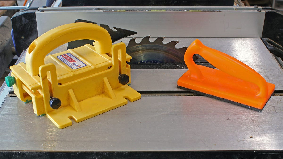 A Microjig Grr-ripper, and orange push block on a table saw.