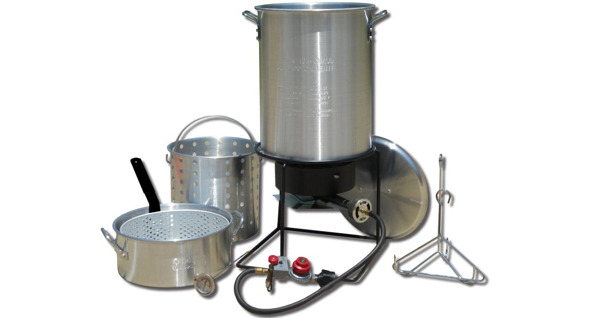 The King Kooker Propane Deep Fryer sitting on the burner next to its lid, a basket, a lifting hook, and a fry pan with Basket