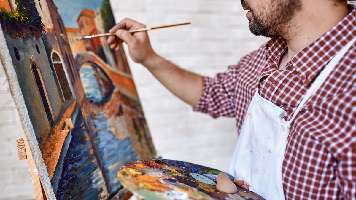 A man painting a European scene on a canvas on an easel.
