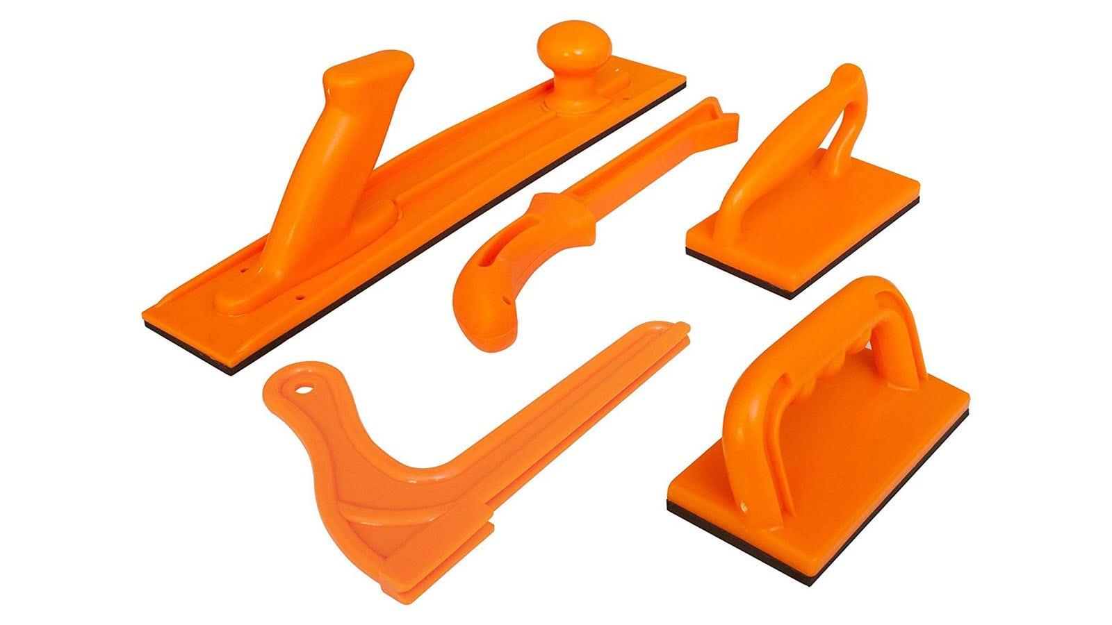 Five push sticks and blocks in a bright orange color.