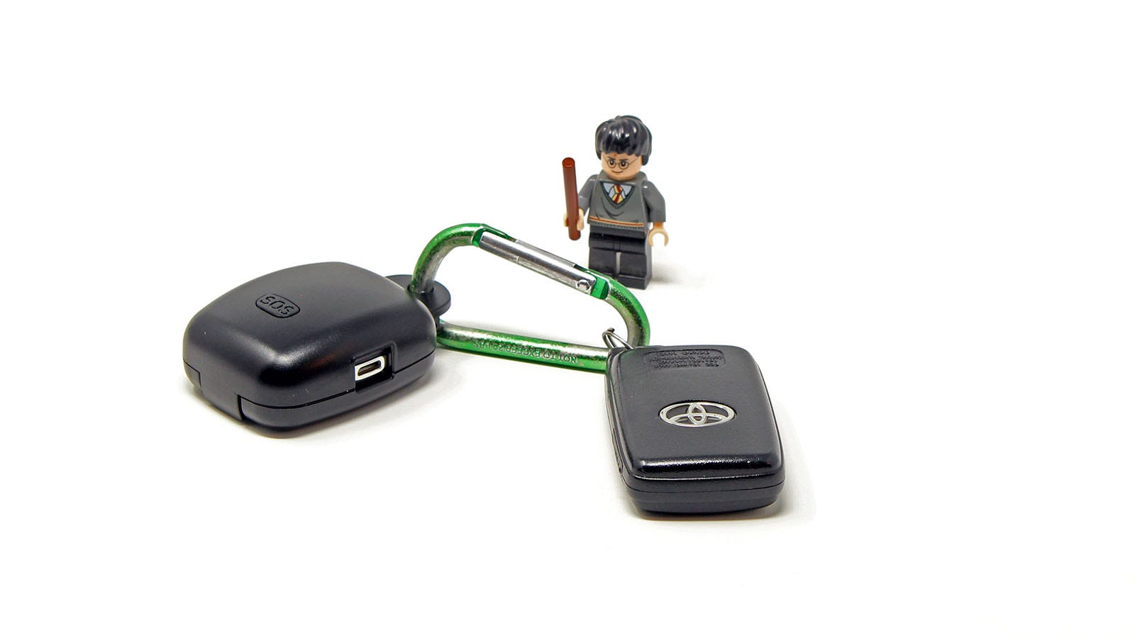 The GeoZilla GPS tracker attached to a similar sized key fob near a Harry Potter lego minifig.