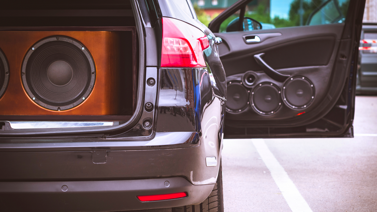 An SUV with a subwoofer in the open trunk, and speakers on the opened passenger's side door.