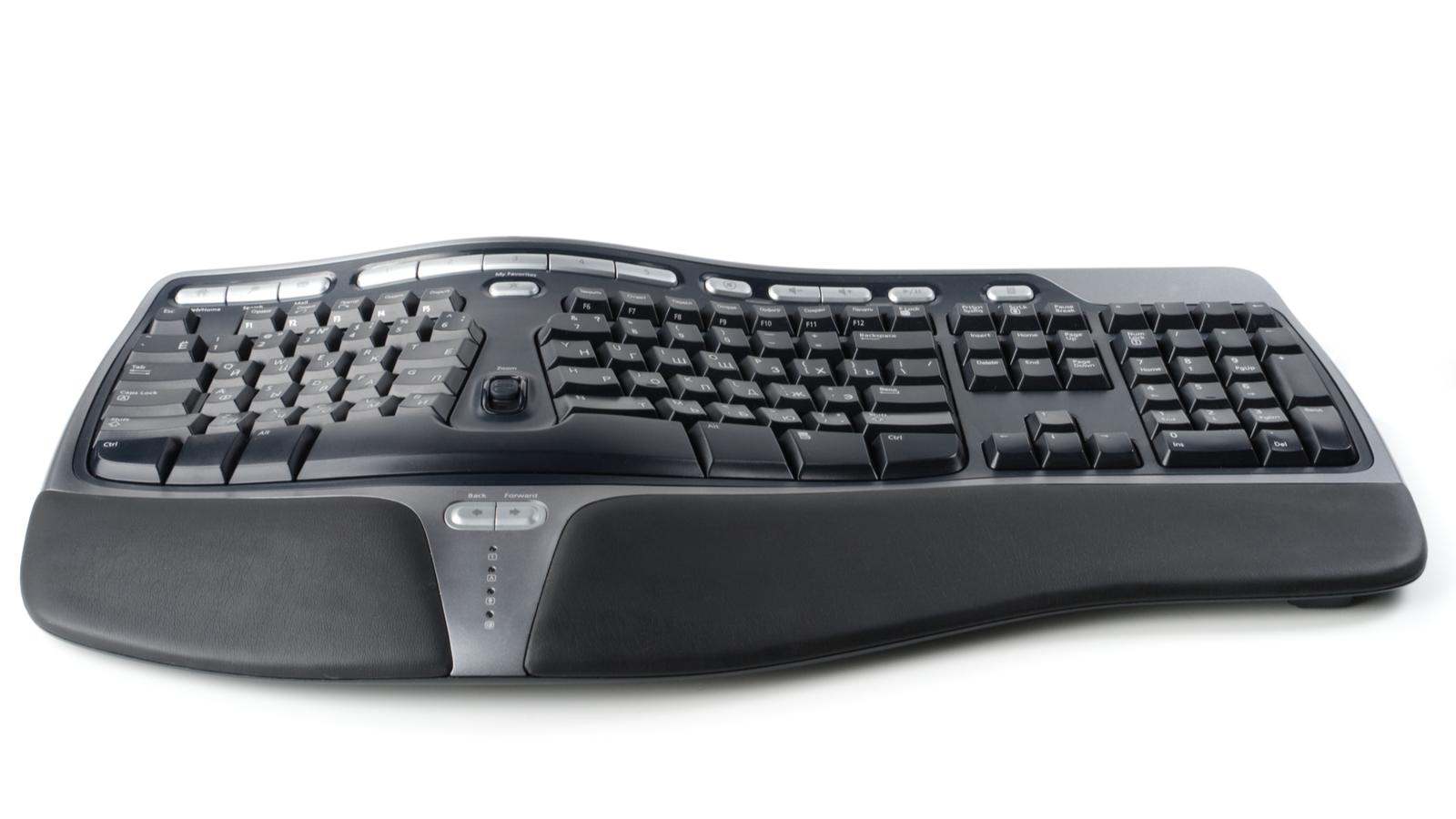 Современная черная эргономичная компьютерная клавиатура на простом белом фоне