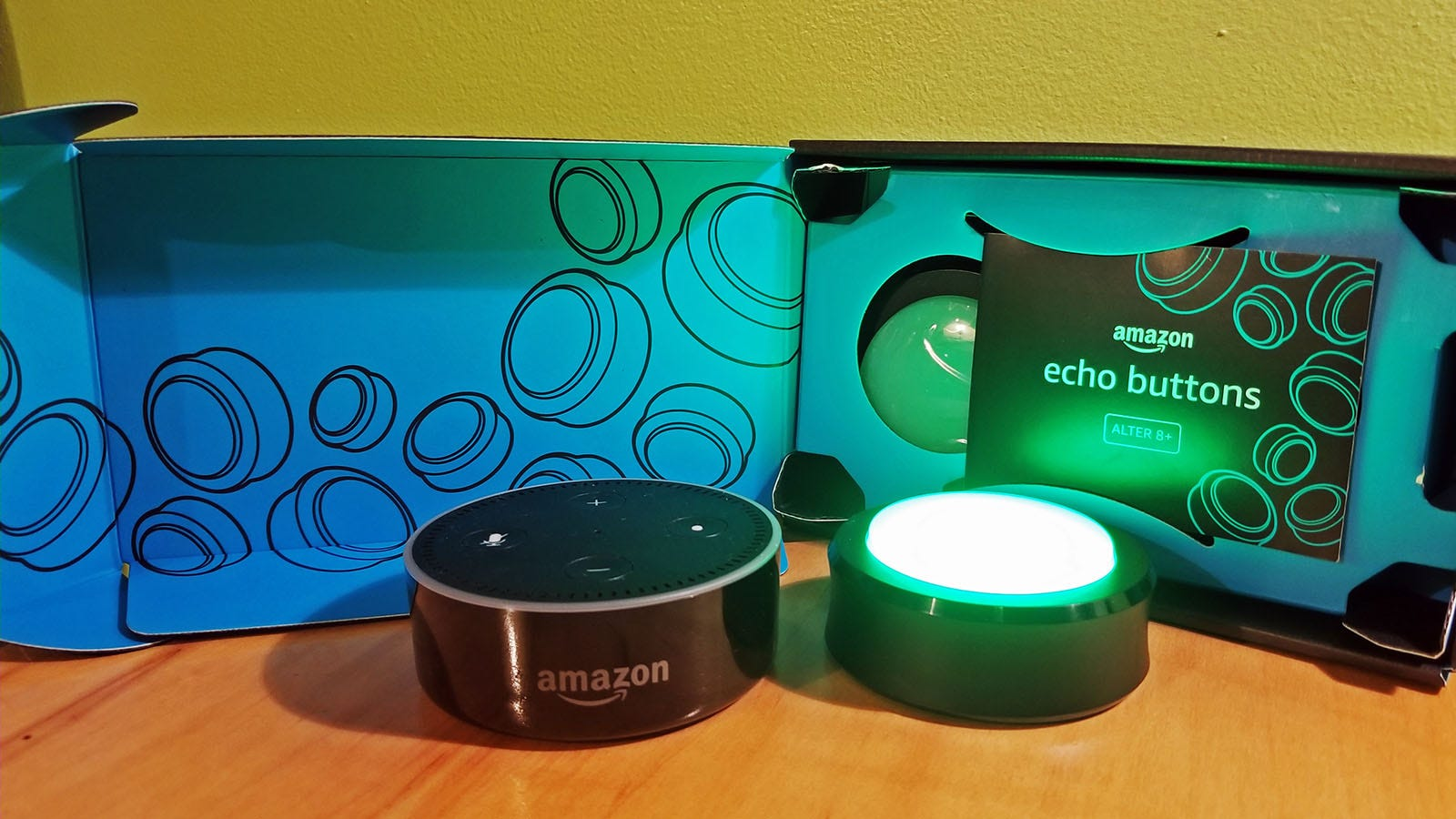 An Amazon Echo and a glowing green Echo button in front of their boxes.